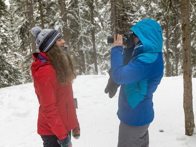 雪に覆われた森林、ジョンストンキャニオン、バンフ国立公園、アルバータ州、缶で写真を撮っている観光客