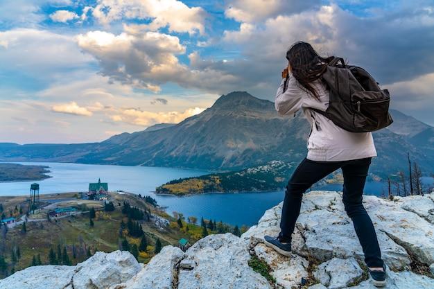 Туристы фотографируют национальный парк уотертон-лейкс в красивых сумерках. пейзаж в осенний сезон листвы. альберта, канада.