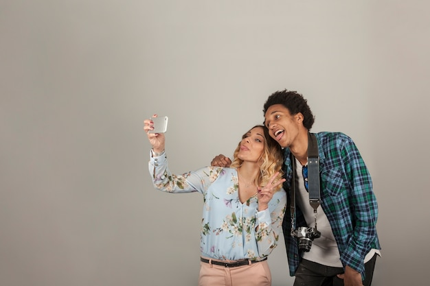 Tourists taking selfie on blank background