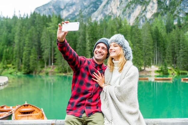 Tourists taking selfie visiting an alpine lake