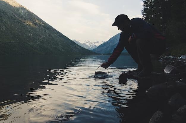 淡水湖から鍋に水を入れて火で調理する観光客