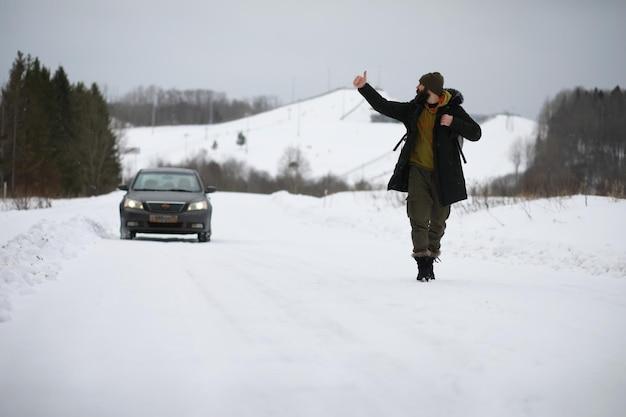 관광객들은 눈 덮인 나라를 여행합니다. 가는 길에 걷고 히치하이크를 합니다.