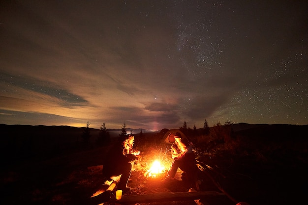 Tourists travelers sitting by burning campfire on mountain valley under starry cloudy sky.