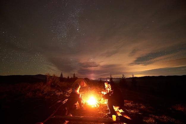 Туристы-путешественники сидят у горящего костра в горной долине под звездным облачным небом.