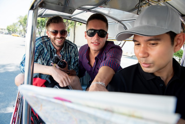 Tourists traveling by local tuk tuk taxi in bangkok thailand