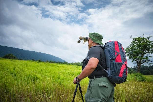 관광객들은 쌍안경을 사용하여 열대 우림의 초원에서 새와 야생 동물을 봅니다. 태국 카오야이 국립공원. 새, 코뿔새, 원숭이 투어. 생태 관광 개념 사진입니다.