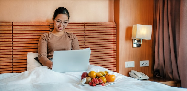 Tourists used laptop and eating fruits on bed in luxury hotel room healthy food concept
