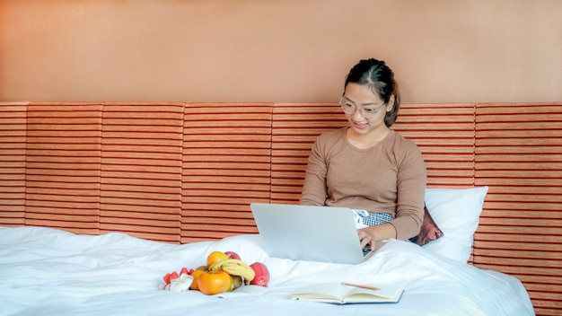 Tourists used laptop and eating fruits on the bed in the luxury hotel room healthy food concept