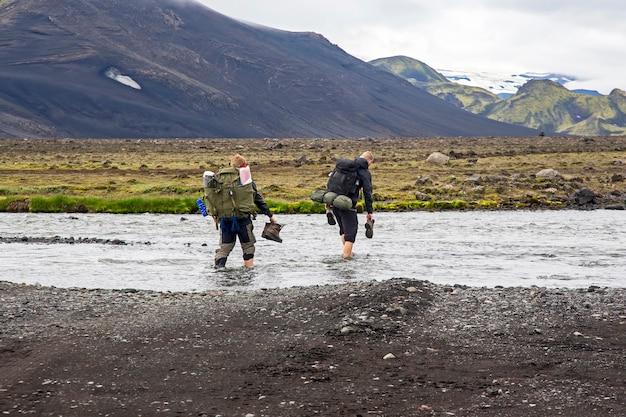 관광객은 아이슬란드의 폭풍우 산 강을 걷다
