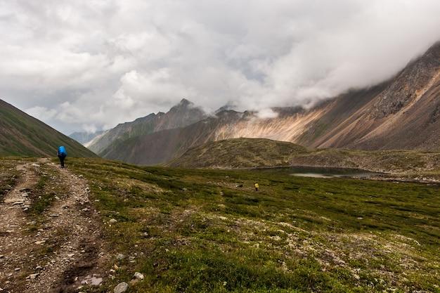 Туристы гуляют по долине по дорожке из камней в горах в пасмурную погоду. небольшое озеро. высокие горные хребты и низкие облака. по горизонтали.