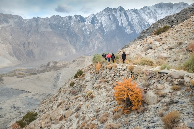 Tourists walking along the hiking path amid karakoram mountain range