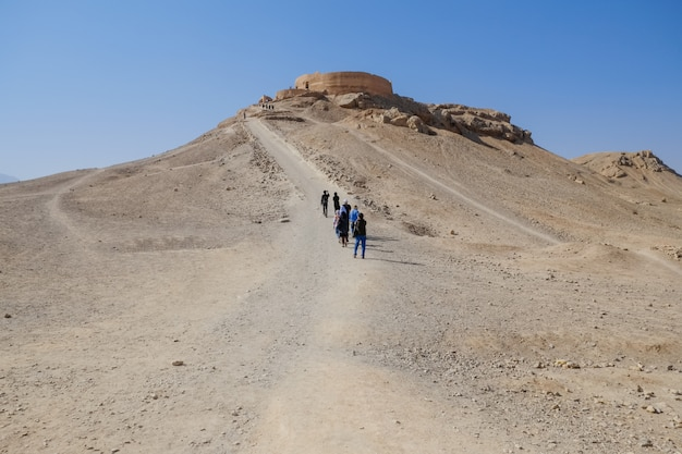 Tourists walking to the ancient buildings of zoroastrian dakhma. persian tower of silence. yazd, iran.