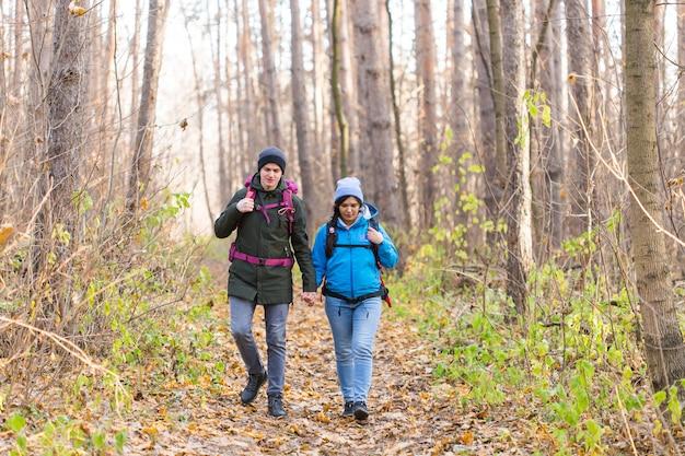 青と黒のジャケットを着たバックパックを持って公園を歩く観光客。