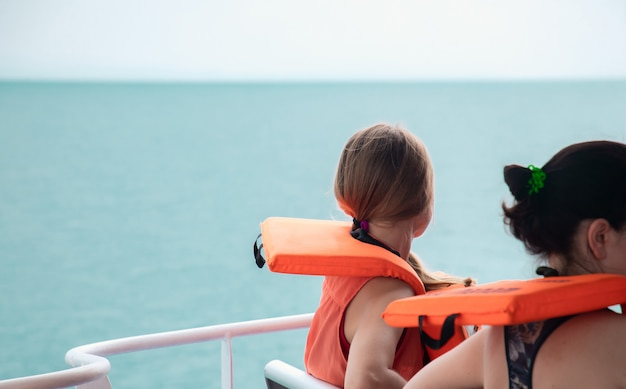 Tourists wear life jackets sitting on the boat.