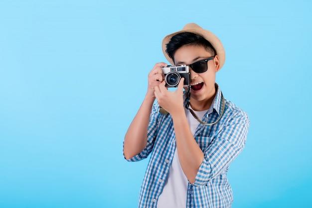 カジュアルな服を着ている観光客は、青のフィルムカメラで写真を撮っています