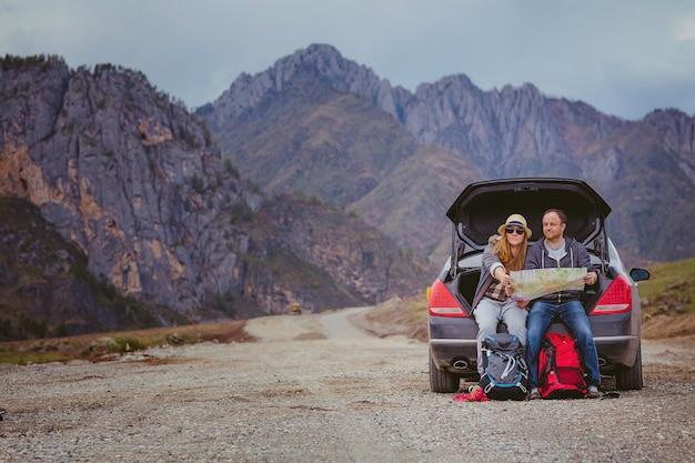 Туристы с картой и рюкзаками в машине в горах