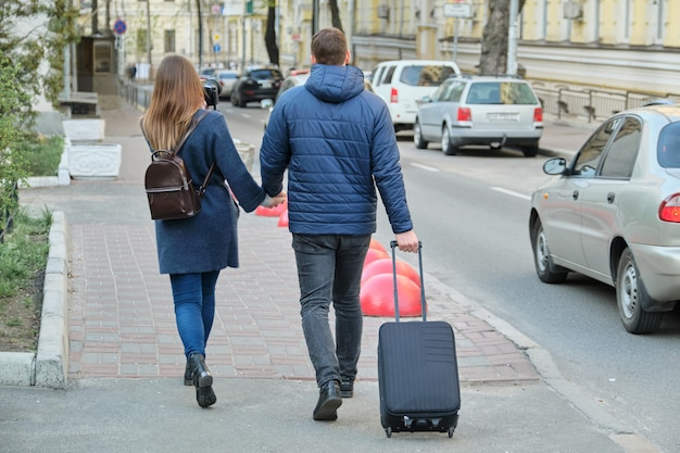 Tourists young couple walking around the city with camera suitcase