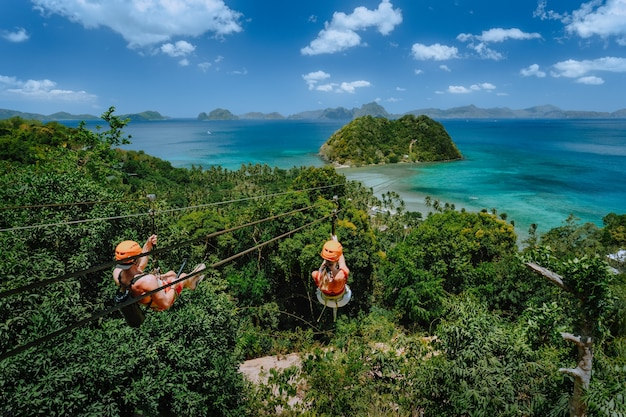 Tourists at zipline glide to the beach. el nido, palawan, philippines.