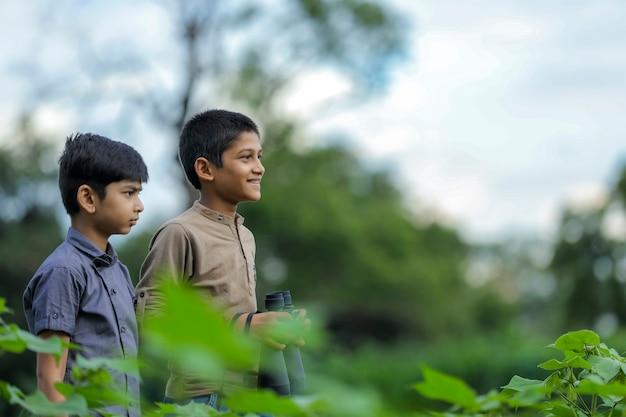 双眼鏡で自然の中で楽しんでいるインドの少年をけん引