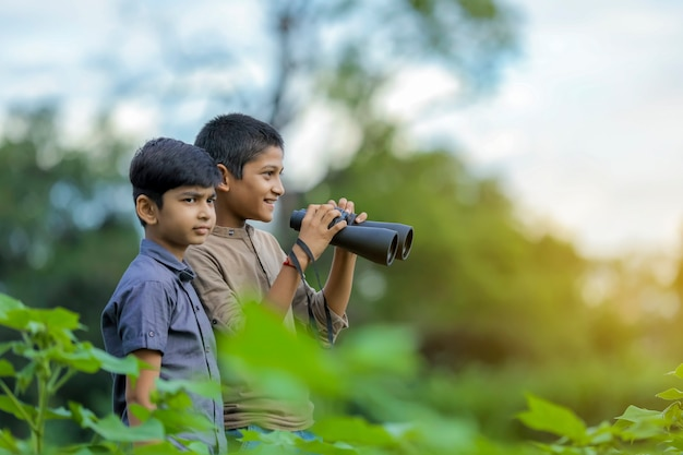 Tow little indian boy enjoys in nature with binoculars