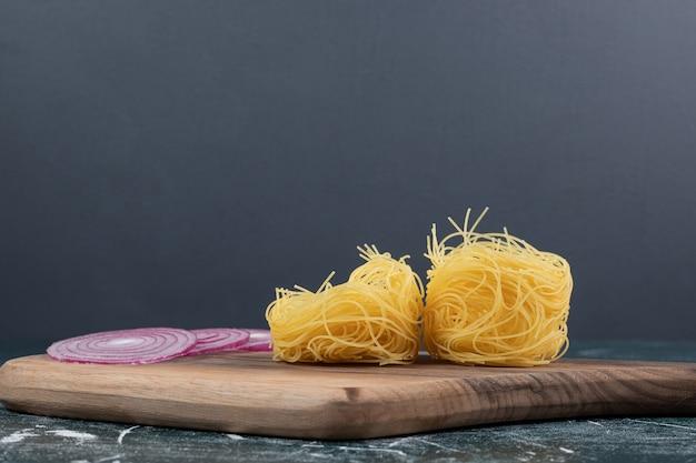 Traino di maccheroni rotondi crudi con fette di cipolla su tavola di legno. foto di alta qualità