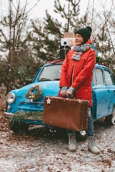 冒険に向けて。冬の森を背景に、古いスーツケースを持った若い女性が古い車でロードトリップを待っています。クリスマス休暇の時間。