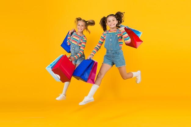 購入に向けて。モダンファッション。キッズファッション。かわいい子供たちがセールシーズンに急いでいます。割引と販売。小さな女の子は買い物袋を持っています。おそろいの衣装。トレンディでファンシー。ファッションショップ。