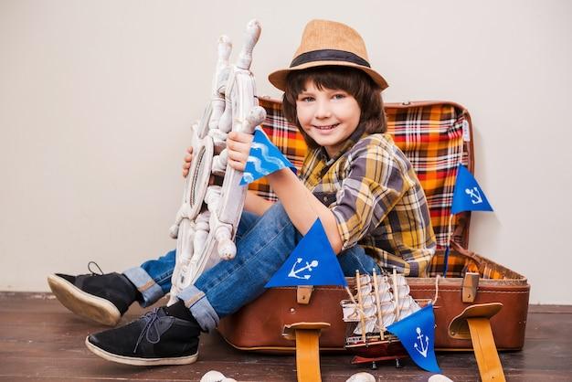 冒険に向けて!帽子をかぶって、スーツケースに座って大きなハンドルを握りながらカメラを見ている少年