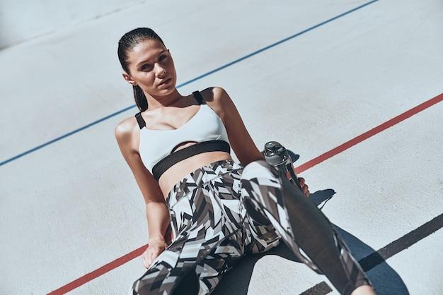 К более здоровому образу жизни. вид сверху молодой женщины в спортивной одежде отдыхает