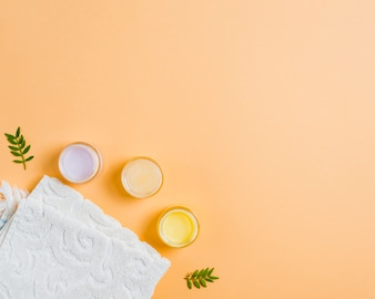 Towel and different moisturizers on colored background