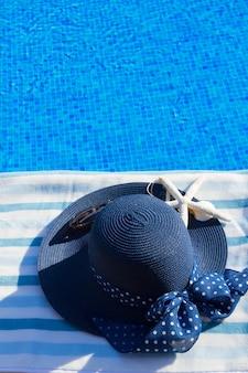 Полотенце и летняя синяя шляпа с ракушками возле бассейна, копия пространства на голубой воде