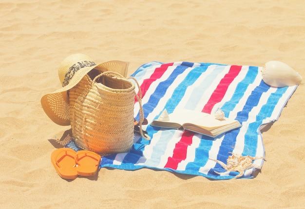 砂浜のタオルと日光浴用アクセサリー、レトロなトーン