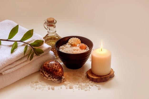 タオル、美容マッサージオイル、葉、貝殻とキャンドルの海塩。