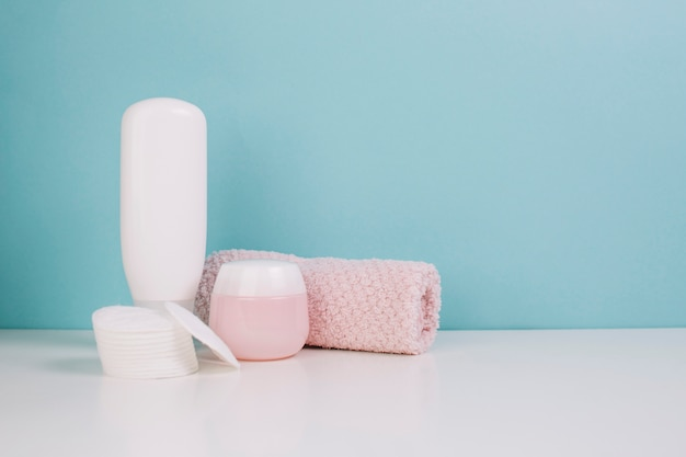 Towel and cotton pads near cosmetics bottle and jar