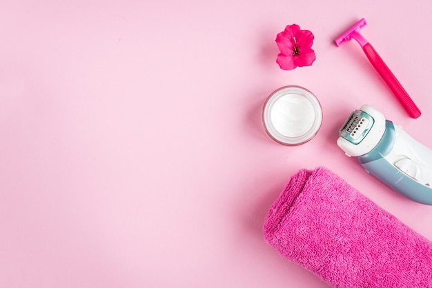 Towel, cream, razor and flower on pink background. flat lay. skincare.