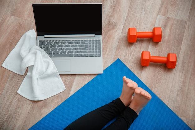 Ноутбук полотенце гантели вид сверху. молодая женщина делает фитнес-тренировки, упражнения на растяжку, используя ноутбук через видеозвонок. женщина в спортивной одежде делает дистанционные занятия йогой, сидя дома.