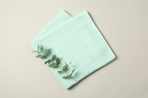 Towel and eucalyptus branch on grey, space for text