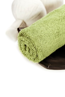 Towel and herbal massage balls over white