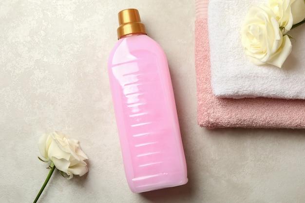 明るいベージュのテクスチャ背景にタオル、洗濯液、バラ