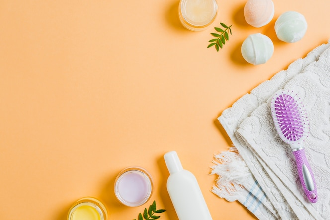 Towel; moisturizers; hairbrush and bath bomb on colored background