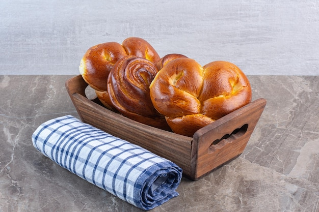 Рулон полотенец и корзина сладких булочек на мраморном фоне. фото высокого качества