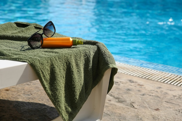 Towel, sunblock cream and sunglasses near the swimming pool