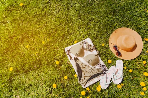 Полотенце с бикини и летние аксессуары на газоне