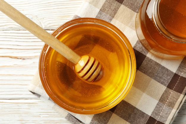 Towel with bowl and jar of honey and dipper on white wooden background