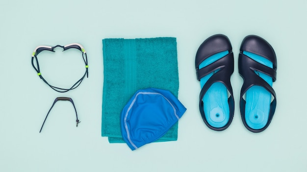 A towel with a cap, slates, swimming glasses and a smart bracelet. accessories for swimming in the pool. flat lay.