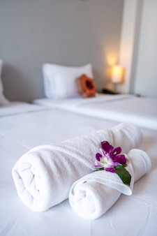 Towel with orchid on bed decoration in bedroom interior for hotel customer.
