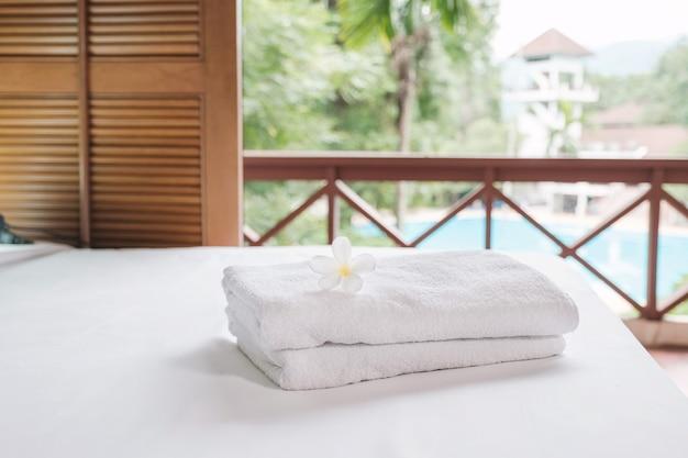 観光旅行の準備ができている高級ホテルの部屋のベッドの上のタオルとプルメリア。
