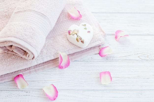 Towels and bath salt and rose petals.
