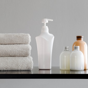 Towels, bottles with shampoo, conditioner, shower milk and handmade soap.