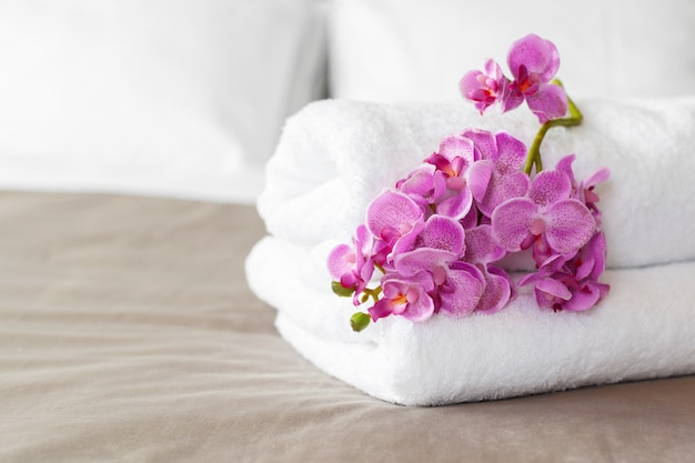 Towels and flower on bed in hotel room